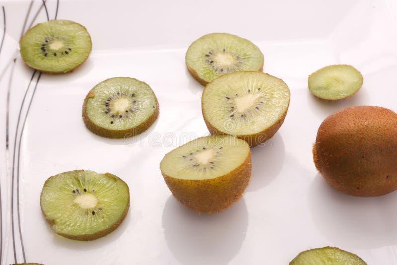 Kiwi fruit on white. Kiwi fruit with kiwi slices on a white background royalty free stock photography