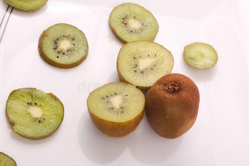 Kiwi fruit on white. Kiwi fruit with kiwi slices on a white background stock image