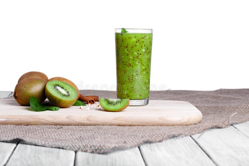 A homemade cocktail with kiwi, mint and grated nuts on a wooden table, isolated on a white background. Organic fruits. royalty free stock photo