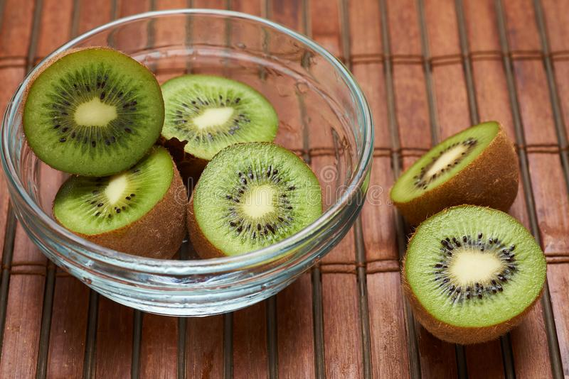Kiwi in a glass plate on a bamboo background stock photo