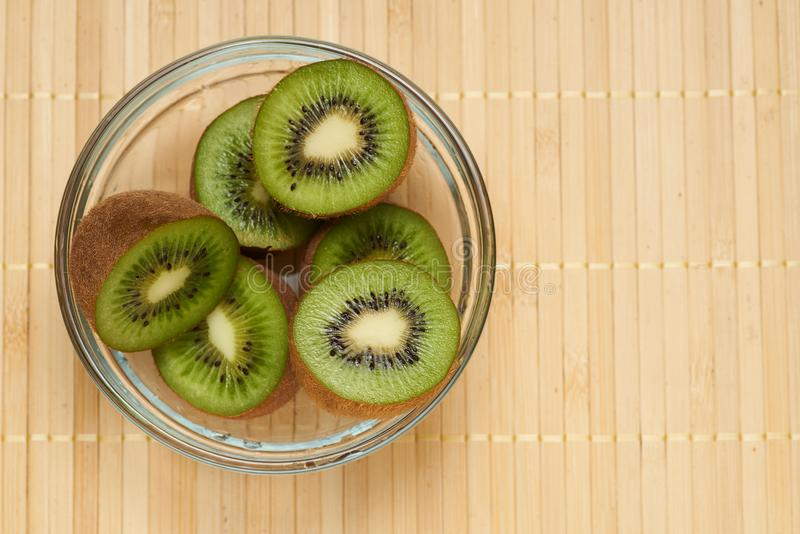 Kiwi in a glass plate on a bamboo background stock photos