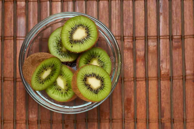 Kiwi in a glass plate on a bamboo background royalty free stock images