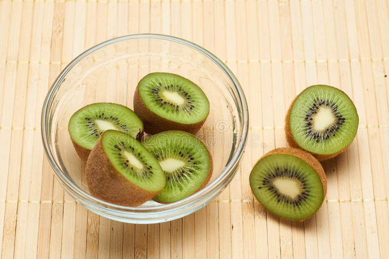 Kiwi in a glass plate on a bamboo brown background royalty free stock photo