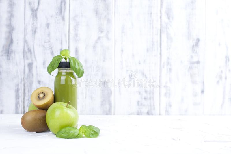 Kiwi, green apple, basil and. juice in a plastic bottle. Detox food. White wooden background. Copy space stock images