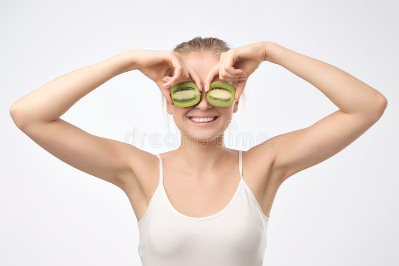 Kiwi Hållande kiwi för sund kvinna för frukt rolig för henne ögon fotografering för bildbyråer