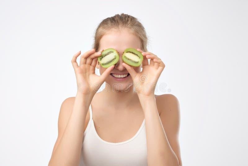 Kiwi. Healthy fruit funny woman holding kiwi fruit for her eyes. royalty free stock image