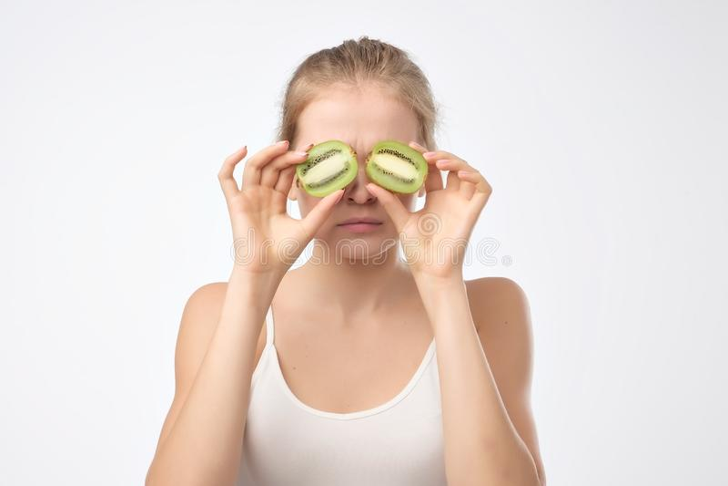 Kiwi. Healthy fruit funny woman holding kiwi fruit for her eyes. royalty free stock photography