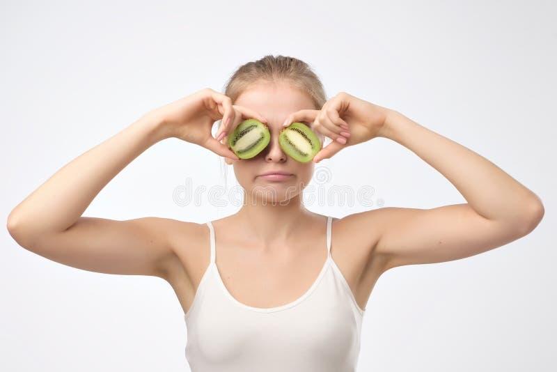 Kiwi. Healthy fruit funny woman holding kiwi fruit for her eyes. stock image