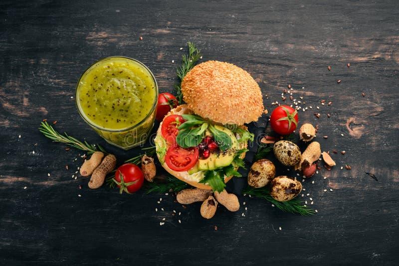 Kiwi i burger na śniadanie z jajami przepiórkowymi i warzywami Na drewnianym tle fotografia royalty free