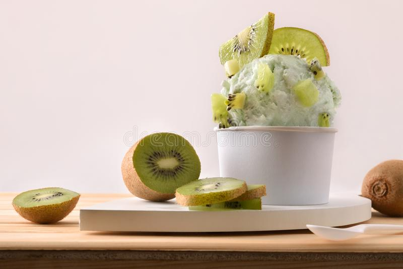 Kiwi ice cream cup decorated with sliced kiwi. Kiwi ice cream cup decorated with pieces and slices of kiwi fruit on a wooden table. Horizontal composition. Front royalty free stock photos