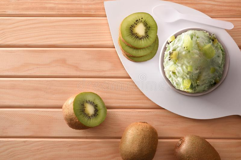 Kiwi ice cream cup decorated with sliced kiwi top. Kiwi ice cream cup decorated with pieces and slices of kiwi fruit on a wooden table. Horizontal composition royalty free stock photos