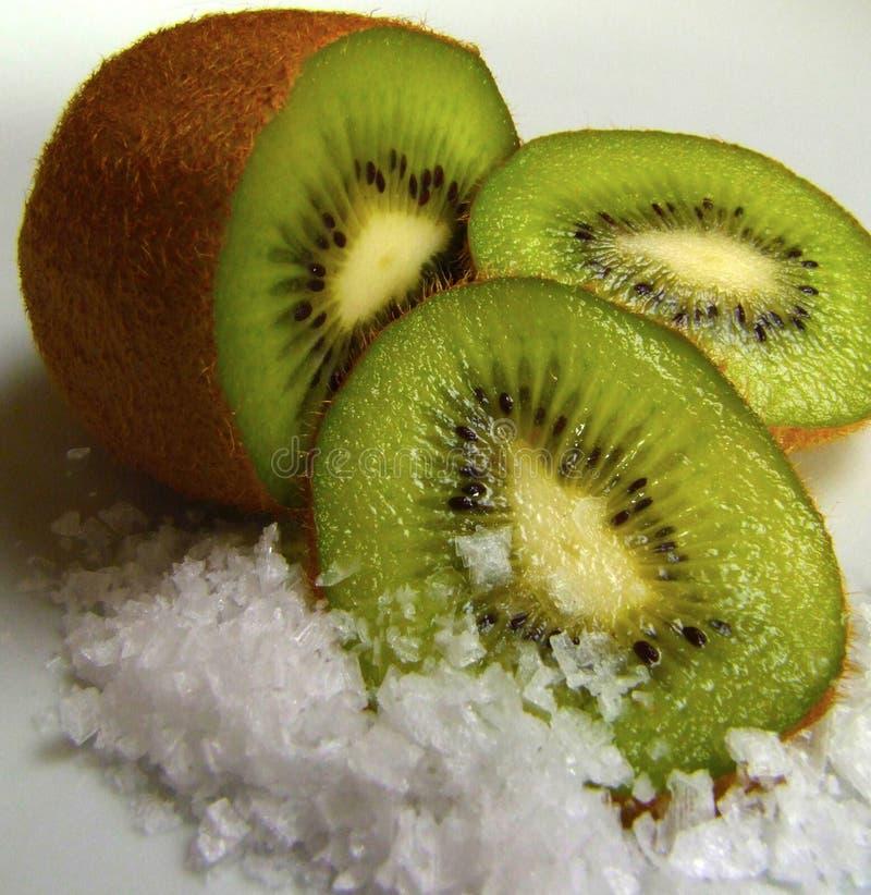 Kiwi and ice. Ripe green kiwi is lying on the cold ice shards stock image