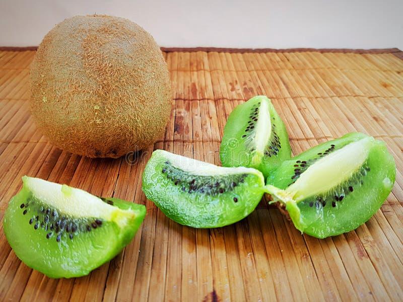 Kiwi ist eine exotische großartig reife Frucht mit geschnittenen grünen Kiwischeiben stockfotografie