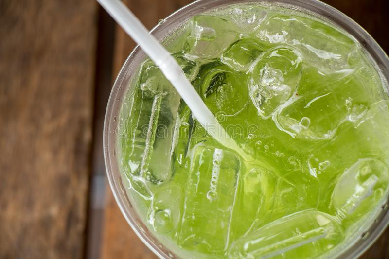 Texture of Kiwi Italian Sod. Kiwi Italian Soda with Ice in glass placed on wooden table royalty free stock photography