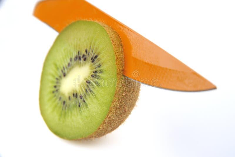 Kiwi and kniffe. Knife cut kiwi slice royalty free stock photo