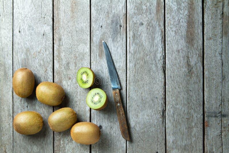 Kiwi och kniv på träbakgrund arkivbild