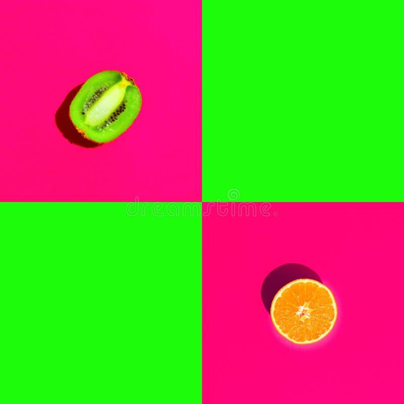 Kiwi orange divisé en deux juteux mûr sur le fond vert de rose au néon lumineux de fuchsia de duotone avec les places vides pour  photographie stock libre de droits