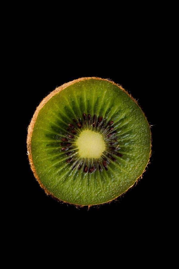 Kiwi over zwarte verfrissing als achtergrond, gesneden deel, schil stock afbeeldingen