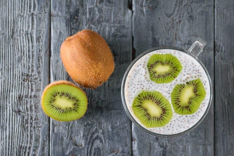 Kiwi owoc i kubek czarny Chia siamy pudding na czarnym drewnianym stole najlepszy widok Mieszkanie nieatutowy zdjęcie stock