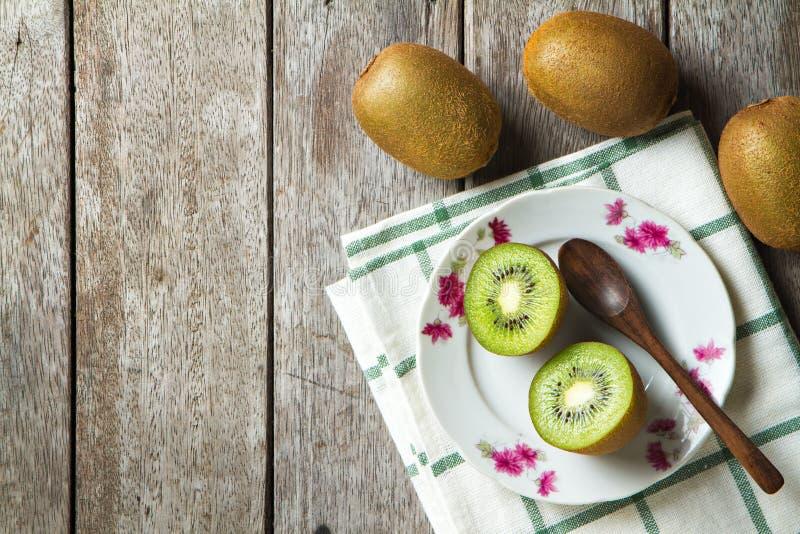 Kiwi på maträtt och sked på träbakgrund royaltyfri bild
