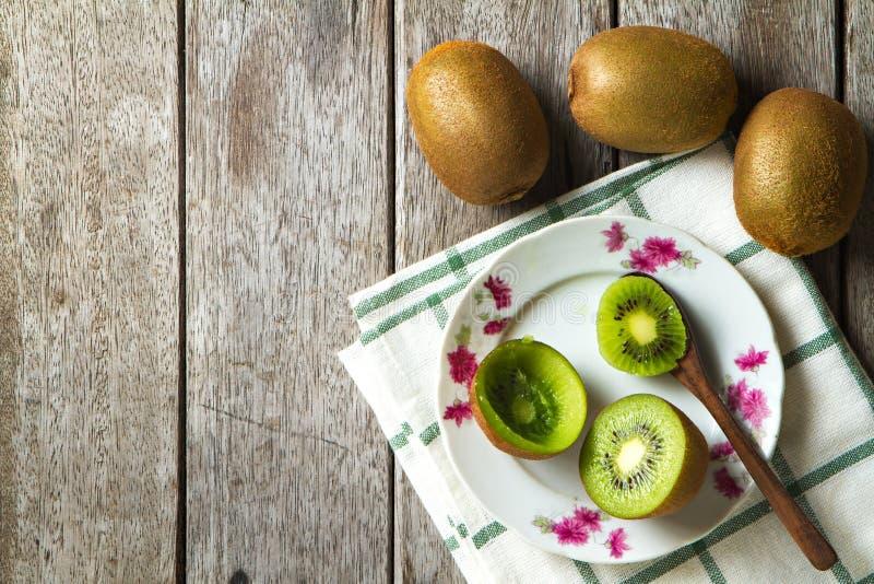 Kiwi på maträtt och sked på träbakgrund royaltyfri foto