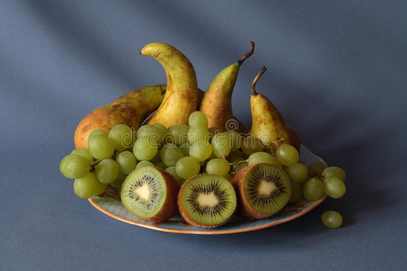 Kiwi, pears and grapes on a plate royalty free stock photos