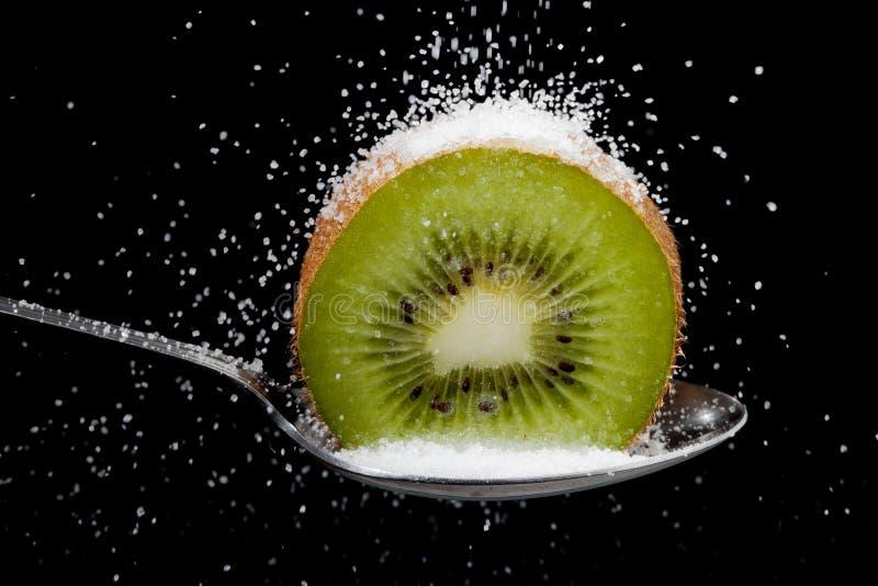 Kiwi schnitt zur Hälfte auf einem Löffel mit Zucker lizenzfreie stockfotografie