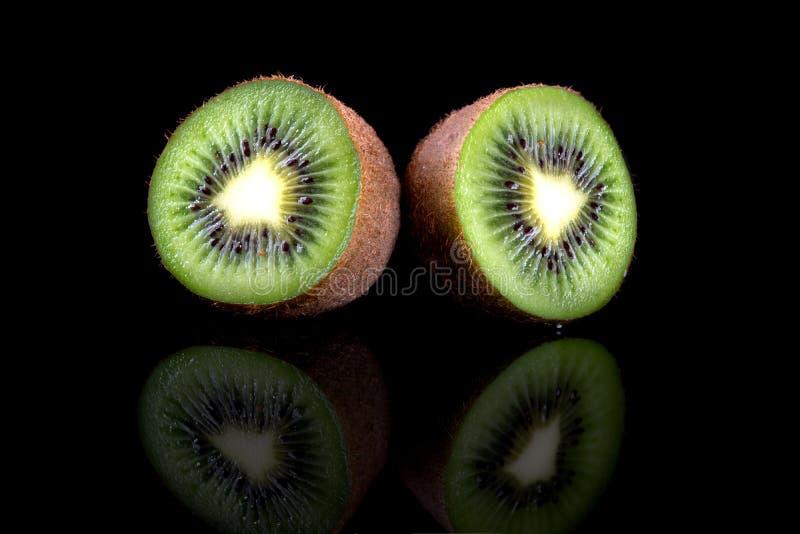 Kiwi skiva av tv? halvor gr?n saftig kiwi Isolerat p? svart royaltyfria bilder