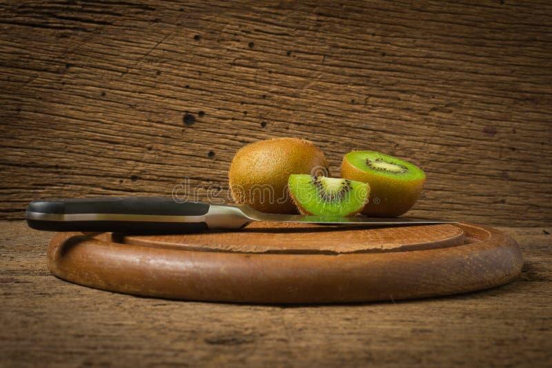 Kiwi Skivat half nytt skärbräda med kniven på gammalt trä royaltyfri fotografi