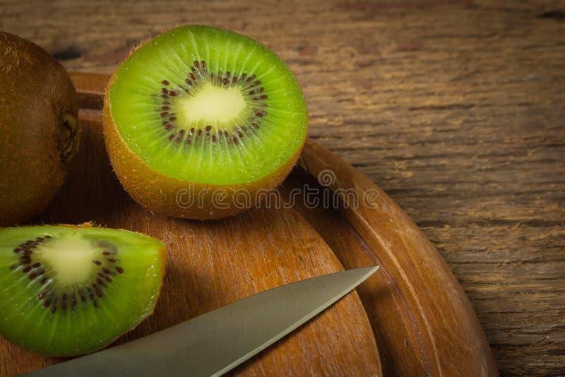 Kiwi Skivat half nytt skärbräda med kniven på gammalt trä arkivfoto