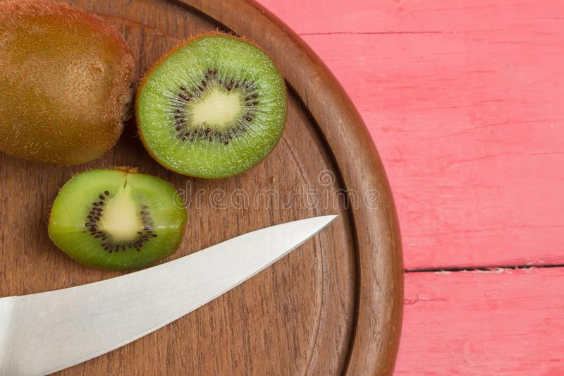 Kiwi Skivat half nytt Skärbräda med kniven på gammalt uppvakta royaltyfri foto