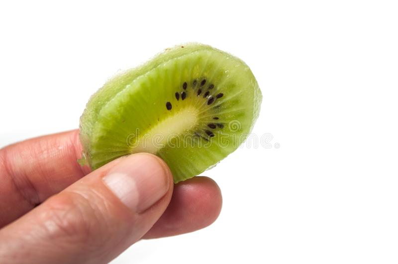 Kiwi slice in hand on white background stock photos