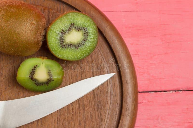 Kiwi sliced demi frais Planche à découper avec le couteau sur vieux courtisez photo libre de droits