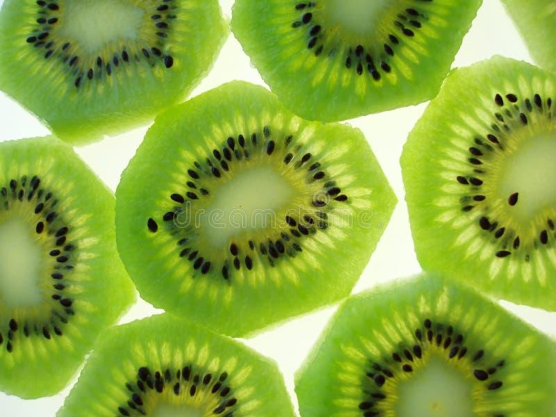 Kiwi slices. Close-up of transparent green kiwi slices on white background royalty free stock image