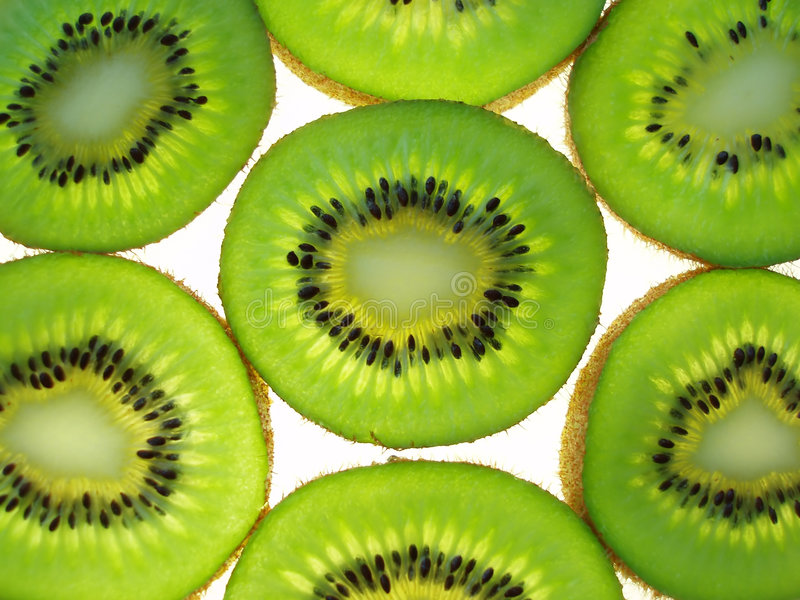 Kiwi slices. Close-up of transparent green kiwi slices on white background royalty free stock photos