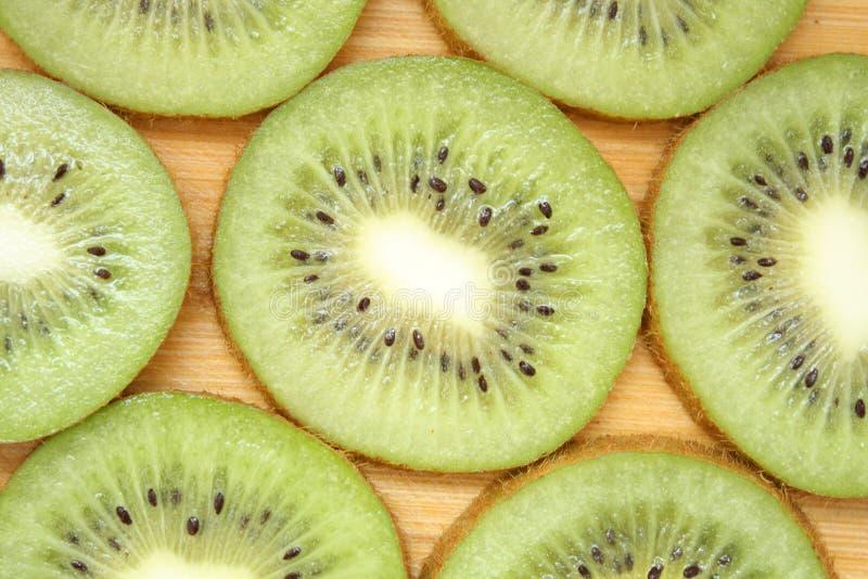 Kiwi Slices. Kiwi Slice on a wood background royalty free stock image