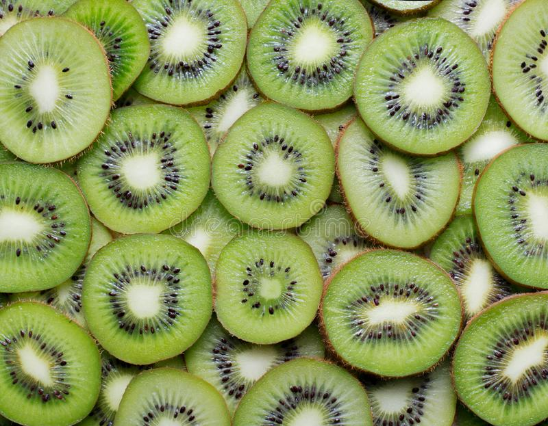 Kiwi slices background. Top view of manu kiwi slices as textured background stock images