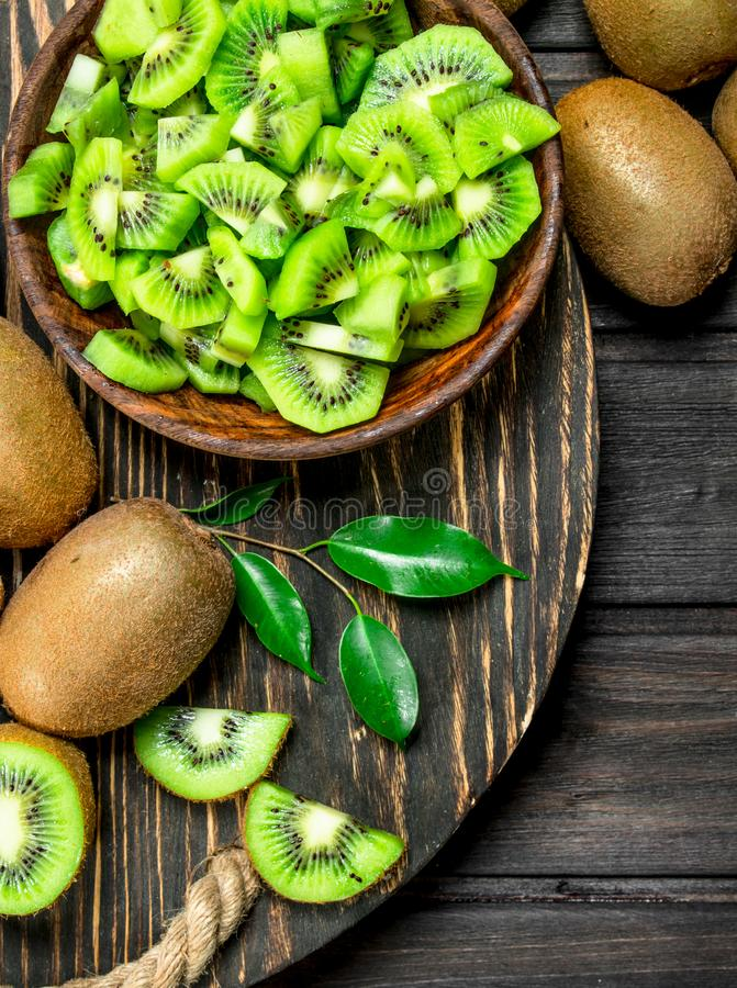 Kiwi slices in a bowl on a wooden tray. On black wooden background stock images