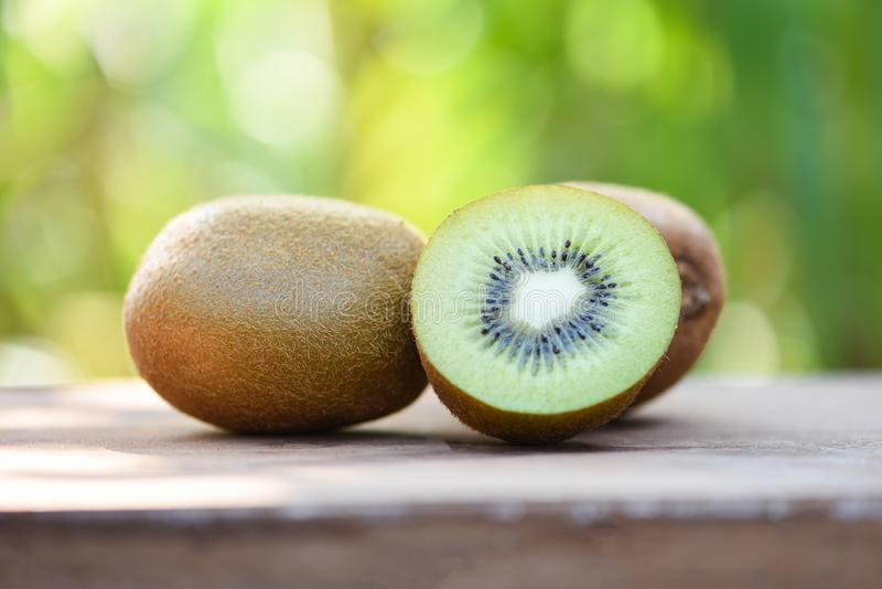 Kiwi slices close up and fresh whole kiwi fruit wooden and nature green background. Kiwi slices close up and fresh whole kiwi fruit on wooden and nature green royalty free stock image