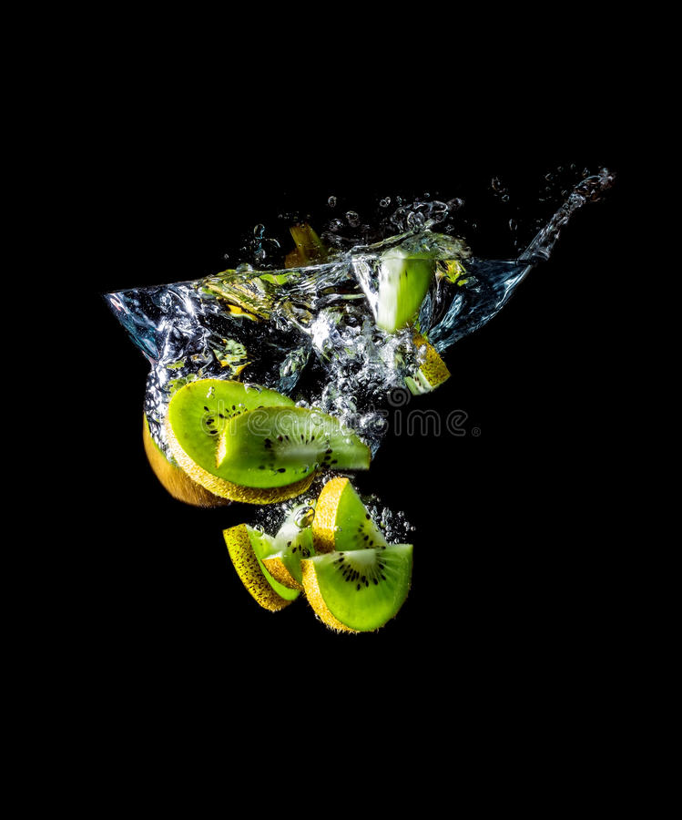 Kiwi slices falling into the water close-up, macro, splash, bubbles, isolated on black. Background stock photography