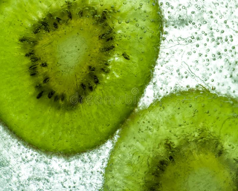 Kiwi slices frozen in translucent ice with air bubbles royalty free stock photo