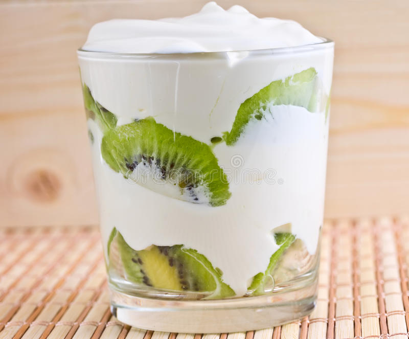Kiwi slices in a glass with cream. Kiwi slices in a glass with whipped cream royalty free stock photos