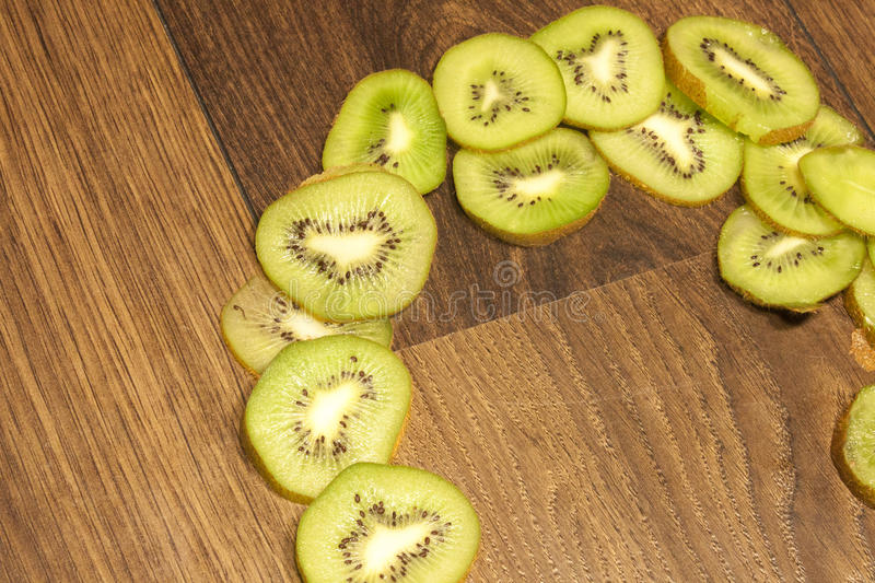 Kiwi slices. Green kiwi slices, on brown, wooden background royalty free stock images
