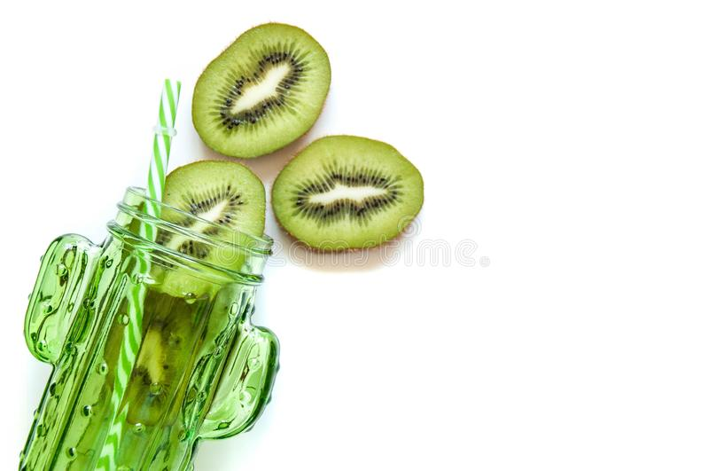 Kiwi slices in a green jar a cactus for cocktails and smoothies. Glass jar for drinks with a straw. Bright summer mood food. Kiwi slices in a green jar a cactus royalty free stock photography