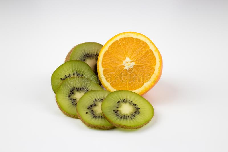 Kiwi slices and half orange on isolated background. Fresh, healthy, ripe kiwi slices with a half orange on isolated white background. multiple uses are possible royalty free stock photos
