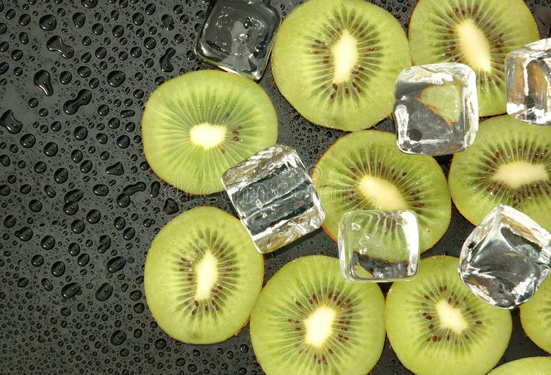 Kiwi slices with ice cubes. On wet black table stock photography