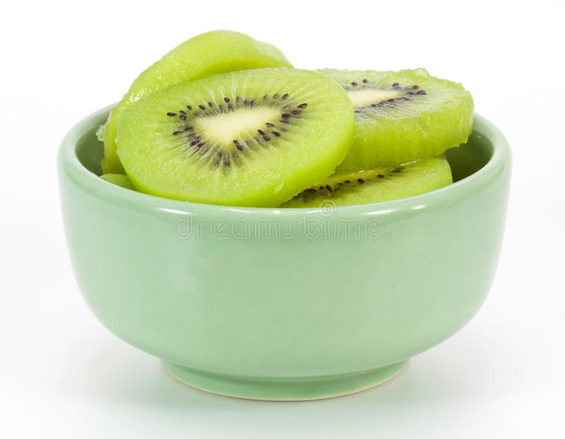 Kiwi slices in a small green bowl. On white royalty free stock images