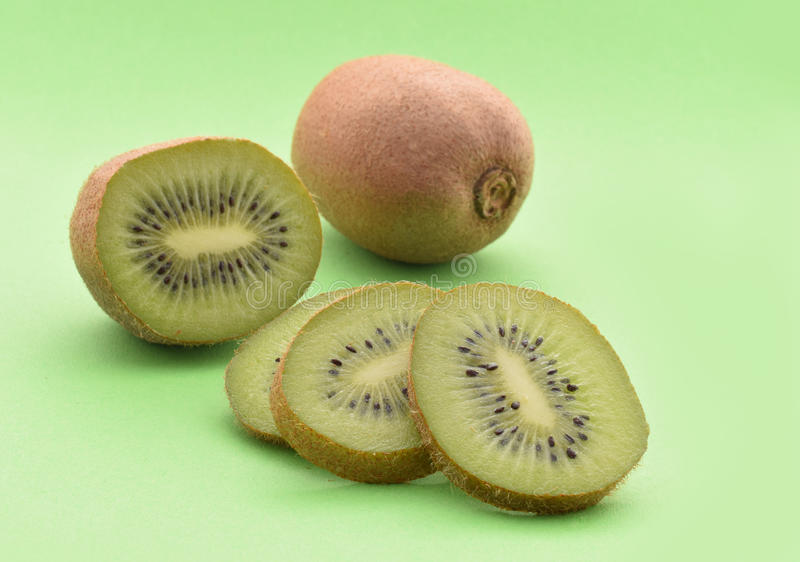 Kiwi. Slices and whole fruit on green royalty free stock photography