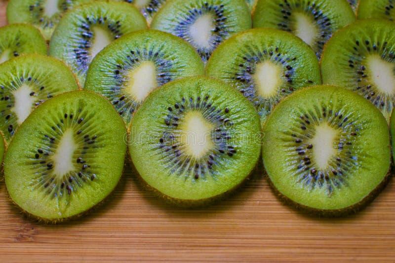 Kiwi slices on a wooden dish. Natural fresh tropical fruit stock photos