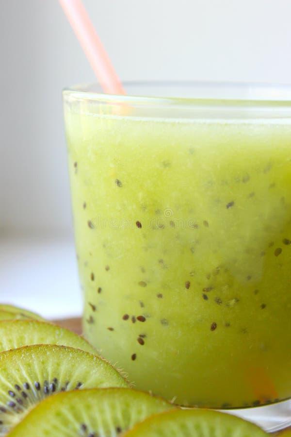 Kiwi Smoothies in einem Glas nahe bei neuen Kiwischeiben auf einem blauen Holztisch Fruchtgetr?nk stockfotos